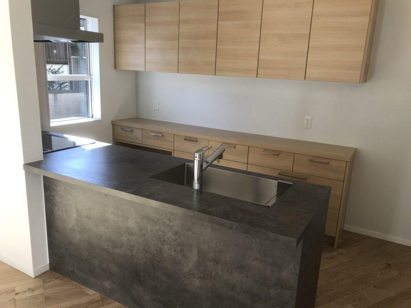 べトングレーのキッチンとナチュラルのカップボードの組み合わせ
